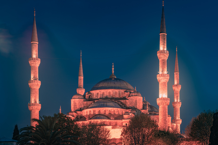 Blue Mosque at night with golden illumination, wide view of Istanbul in dusk. Sultanahmet Camii mosque with six minarets - famous islamic monument of the Ottoman architecture in Turkey.