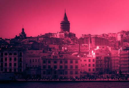 Istanbul cityscape in Turkey with Galata Tower, 14th-century city landmark. Vintage looking image with washed out colors and red color cast Imagens