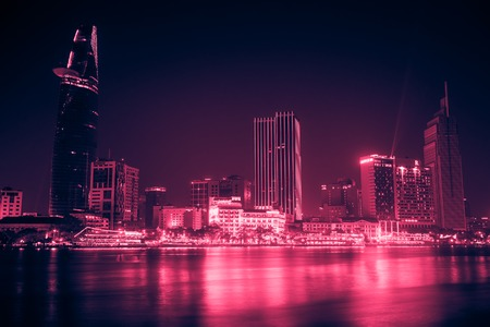 Cityscape of Ho Chi Minh at night with bright illumination. Vintage looking image with washed out colors and red color cast 免版税图像