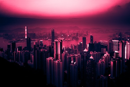 Skyscrapers of Hong Kong in China, Asia. Night view of the city life. Vintage looking image with washed out colors and red color cast Stock Photo