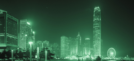 Hong Kong Business District at Night. Corporate building at the back and busy traffic across the main road at rush hour
