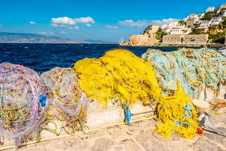 Colorful fishing nets in the harbour of a small fishing town on the coast of the Saronic island of Hydra in Aegean sea, Greece