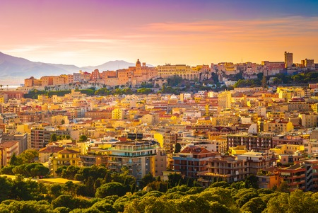 Sunset on Cagliari, panorama of the old city center with traditional colored houses with beautiful yellow-pink clouds, Sardinia Island, Italy Фото со стока