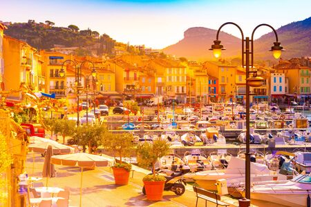 Beautiful landscape with Chateau de Cassis castle on top of hill and close up of boats moored in harbourin morning light in Cassis, France