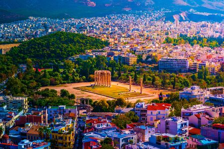 Aerial photo of iconic pillars of Temple of Olympian Zeus and world famous Acropolis hill with masterpiece Parthenon on top at the background, Athens historic center, Attica, Greece