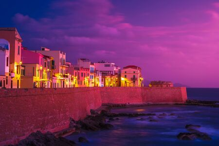 Historical center of Alghero, Sardinia, Italy. Beautiful photo of coastline fortres and houses with night illlumination.