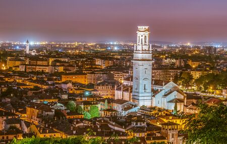 The white bell tower of the Cathedral of Verona in Italy at sunset. Night lights and purple sky above the famous italian city.