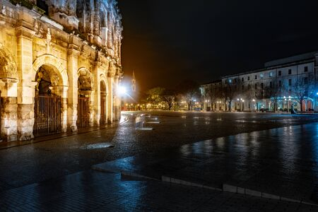 Panorama of illuminated Roman amphitheater in French city of Nimes at night. Beautiful picture of travel destination in France. Foto de archivo - 133745216