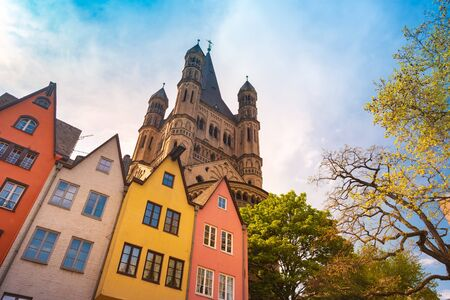Colorful buildings along an embankment and the High Cathedral of St. Peter in Cologne in Germany. Beautiful photo of historical architecture against sun.