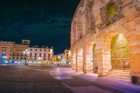 Verona, Italy. Ancient amphitheater Arena di Verona in Italy like Rome Coliseum with nighttime illumination and evening blue sky. Veronas italian famous ancient landmark theatre. Veneto region. Stock fotó