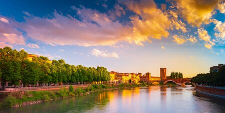 Panoramic view to Bridge Ponte Pietra in Verona on Adige river. Veneto region. Italy. Sunny summer evening with blue dramatic sky with clouds. Ancient european italian terracotta color houses