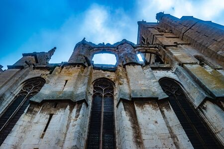 Gothic Cathedral of Narbonne seen from ground with dark architectural structures against sky and clouds, city in the south of France. Stock fotó