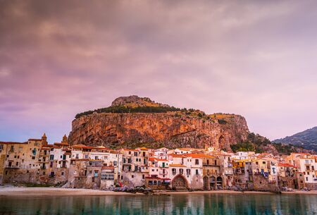 Amazing old houses on the coast of Tyrrhenian sea in beautiful Cefalu, Sicily, Italy. Behind the buildings marvelous rock overlooking the coast. The Sicilian city is a popular tourist attraction.