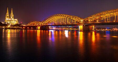 Sonnenunterganghimmel mit Farben und Wolken über der Skyline der Stadt Köln mit Brücke und Kölner Dom, Abendszene über Köln Köln-Stadt mit Kölner Dom Dom hinter der Hohenzollernbrücke. Standard-Bild