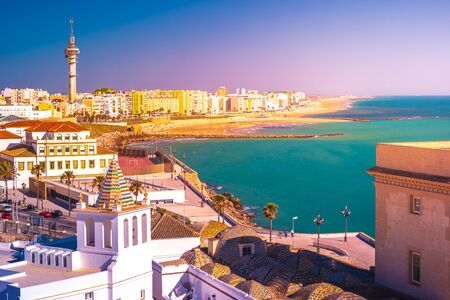 Aerial view of the roofs of historical part of Cadiz, Spain, with the beach and modern city visible in distance.