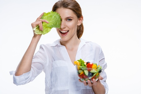 Young beautiful woman with vegetable salad bowl in one hand and cabbage leaf in other hand isolated on white background Stock Photo