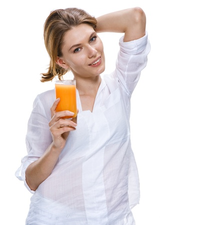 Young beautiful woman with glass of orange juice isolated on white background Фото со стока