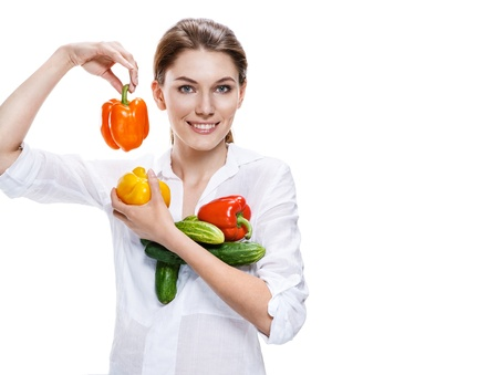 weight reduction plan: promo girl holding a paprika and cucumbers - isolated on white background