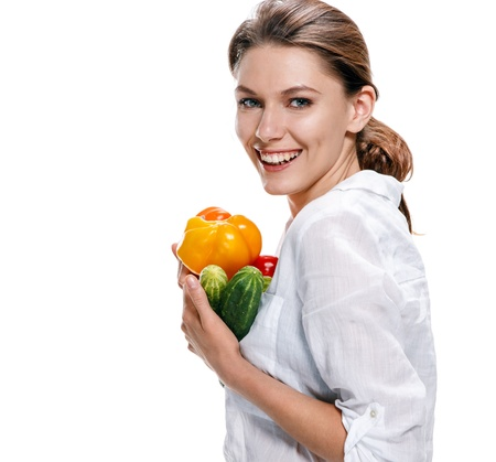 promo girl holds yellow paprika and green cucumbers - isolated on white background