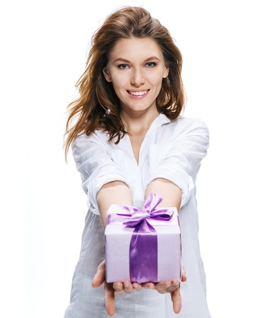 sincere girl: Young beautiful woman gives gift in box isolated on white background Stock Photo