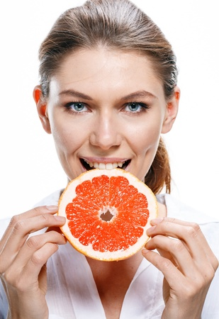 what to eat: Young beautiful woman eat grapefruit isolated on white background