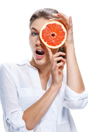 promoter: Young beautiful woman with the slice of grapefruit in front of her eye isolated on white background