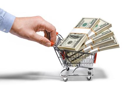 cassa supermercato: uomo d'affari s mano in acciaio carrello della spesa pieno di pile di denaro - isolato su sfondo bianco
