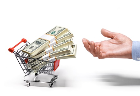businessman s hand   shopping cart full of stacks of american dollar banknotes - isolated on white background Stock Photo - 21645674