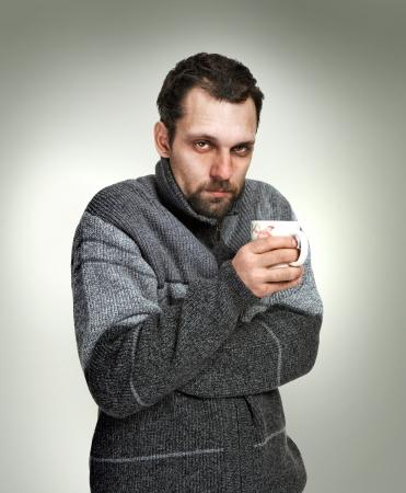 카메라를 찾고 회색 배경에 고립 된 손에 차 한 잔을 들고 회색 스웨터를 입고 감기, 아픈 사람