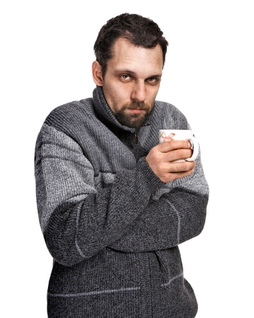 affected: Sick man, affected by cold, dressed in grey sweater holding a cup of tea in hands isolated on white background Stock Photo