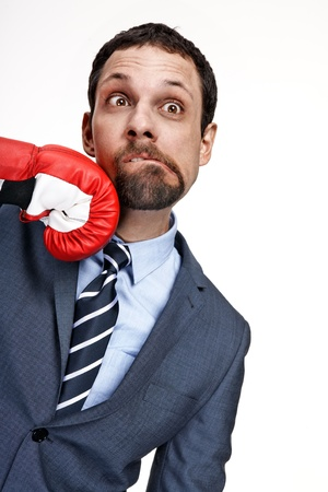 Young business man struck by hand in boxing glove isolated over white background photo