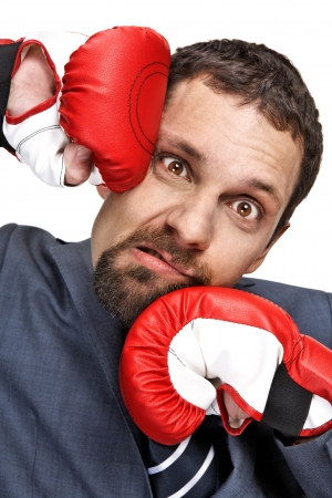 struck: Close-up young businessman struck in the face by hands in boxing gloves isolated on white background