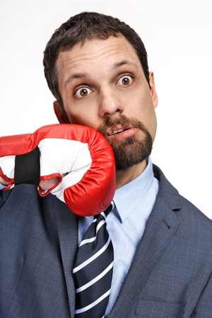 Close-up young business man struck by hand in boxing glove isolated on white background photo
