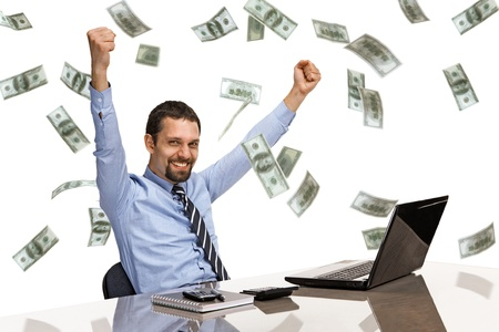 money rain: businessman with his hands raised while working on laptop with money rain
