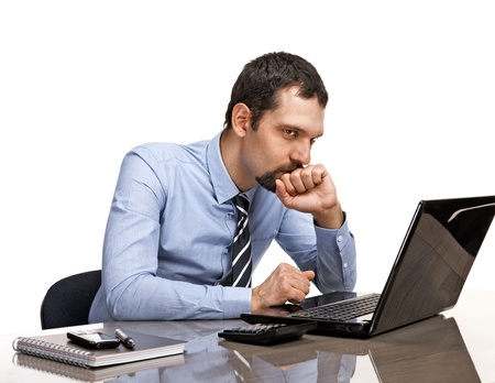 thoughtful businessman at office desk looking on laptop isolated on white background