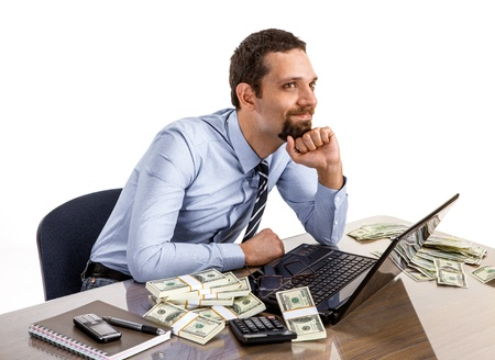 Successful smiling businessman with a lot of dollar stacks at the desk isolated on white background photo