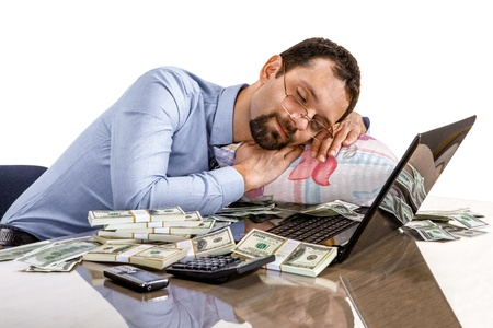 exerted: Worried businessman sleeping at office desk being overloaded with work and accounting money