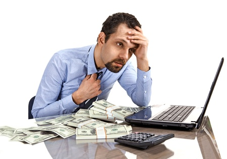 exerted: Worried businessman sitting at office desk being overloaded with work and accounting money Stock Photo