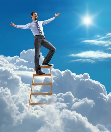 Successful businessman with open arms standing at the top of ladder high in the sky Stock Photo