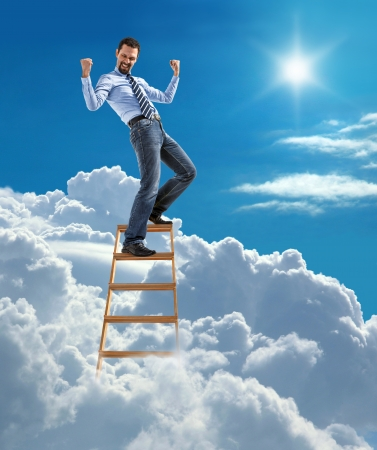 breakthrough: young modern businessman excited with his success standing at the top of ladder high in the sky