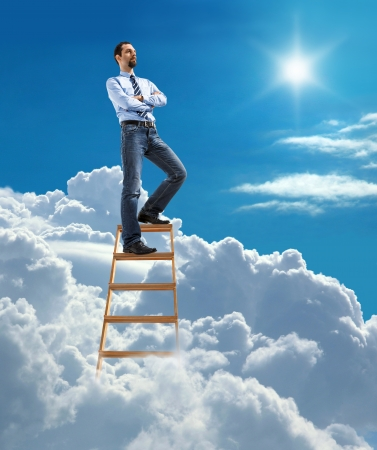 great idea: Young confident businessman standing at the top of ladder high in the sky and looking for new opportunities