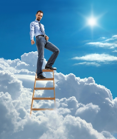 Young confident businessman standing at the top of ladder high in the sky and showing down by the hand with forefinger photo