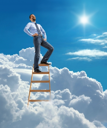 ascend: Laughing confident businessman standing at the top of ladder high in the sky Stock Photo