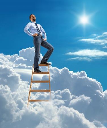 Rire confiant d'affaires debout au sommet du haut de l'échelle dans le ciel