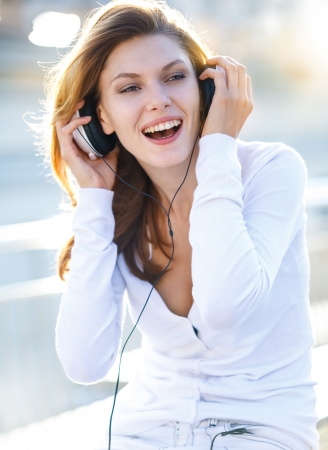 Delightful young woman taking her headphones off photo