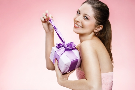 Young beautiful girl with a gift box ribbon photo