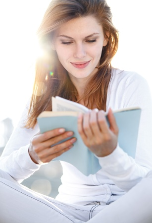 Delightful young woman reading a book photo