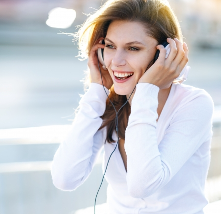 Pleasant young woman puts her headphones on photo