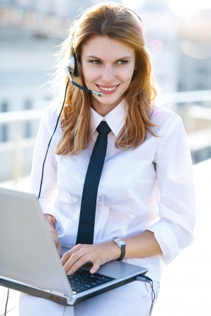 Busy call center operator works at laptop photo
