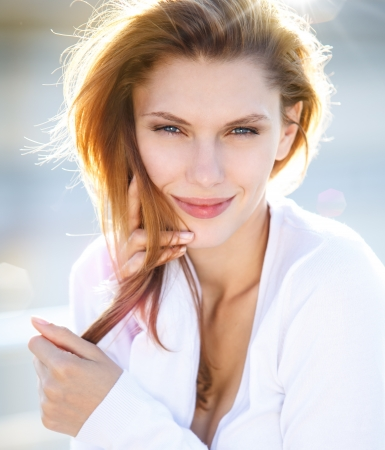 Delightful young woman holds her hair photo